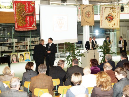 Das Bild zeigt Herrn Oberbürgermeister Gerd Hager mit dem 1. Vorsitzenden Klaus Link. Im Hintergrund das Bläserensemble der Jugendmusikschule.